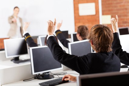 high school students hands up in computer class